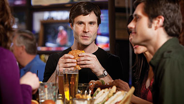 guy holding a burger sitting at a table with friends